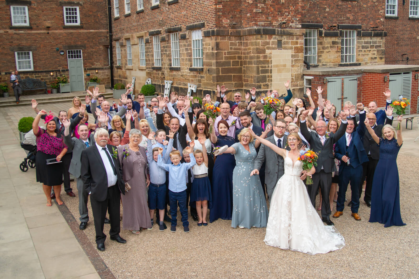 All the wedding guests stand in a large group and cheer from the courtyard of the west mill derby