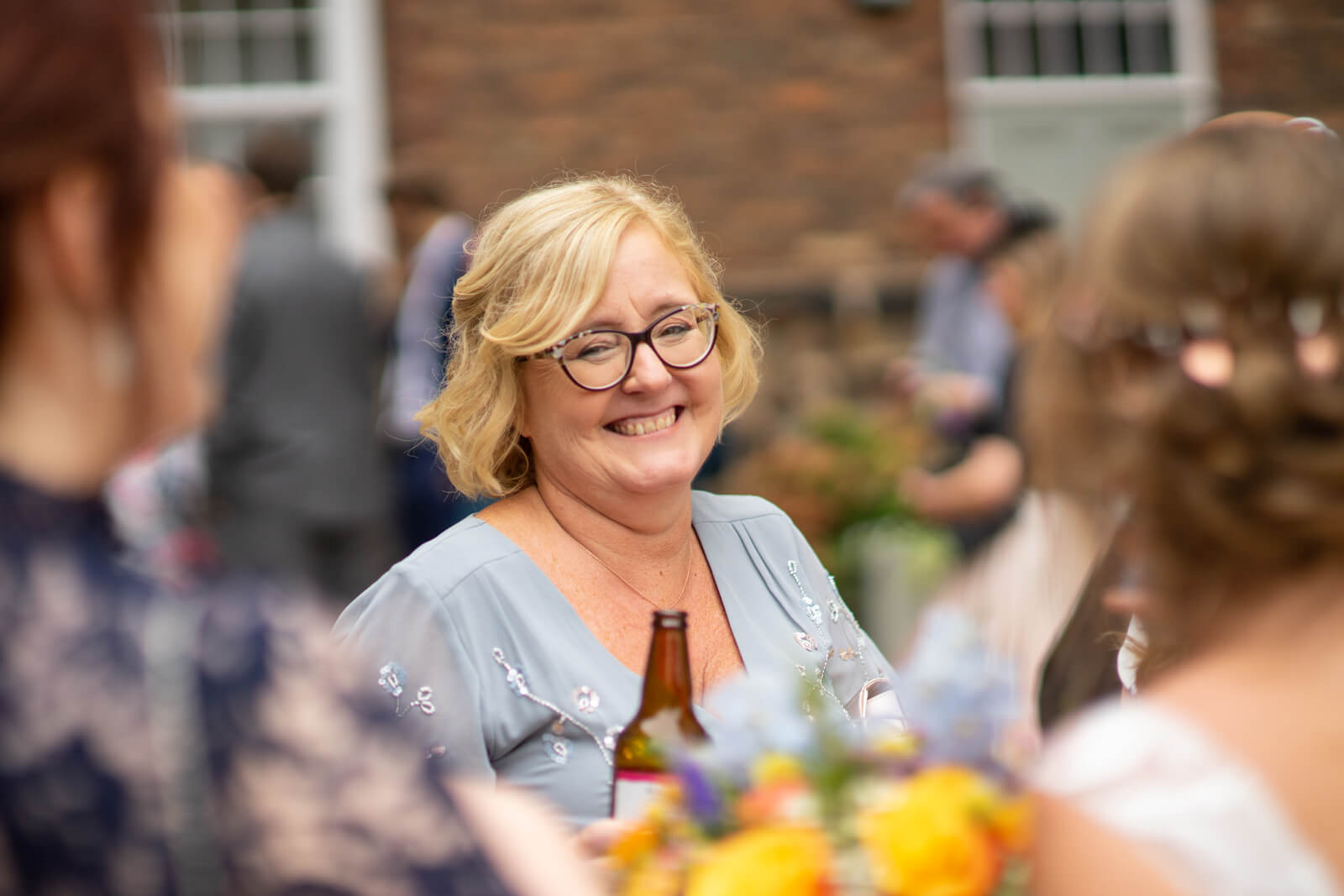 Mother of the bride laughs at the camera during the drinks reception