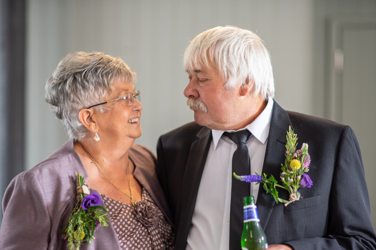 Aunt and Uncle of the groom look at each other and smile