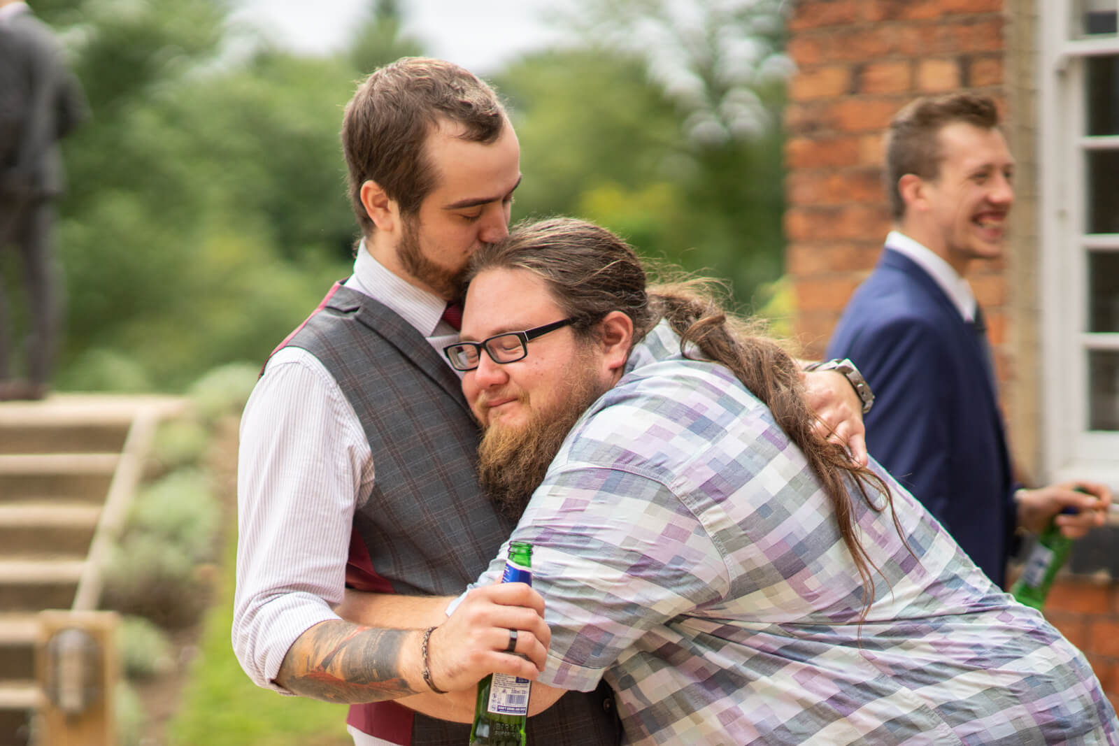 Two male guests mess about and hug each other during the reception