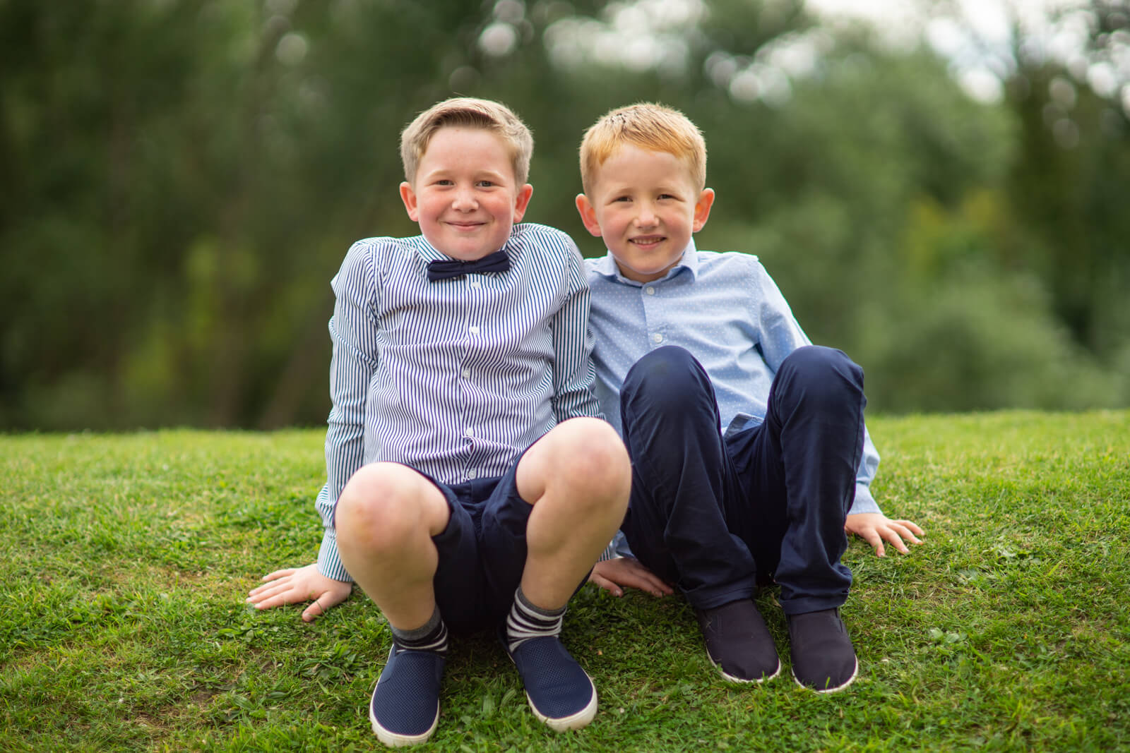 Two cheeky young lads in bow ties sit on a grass bank