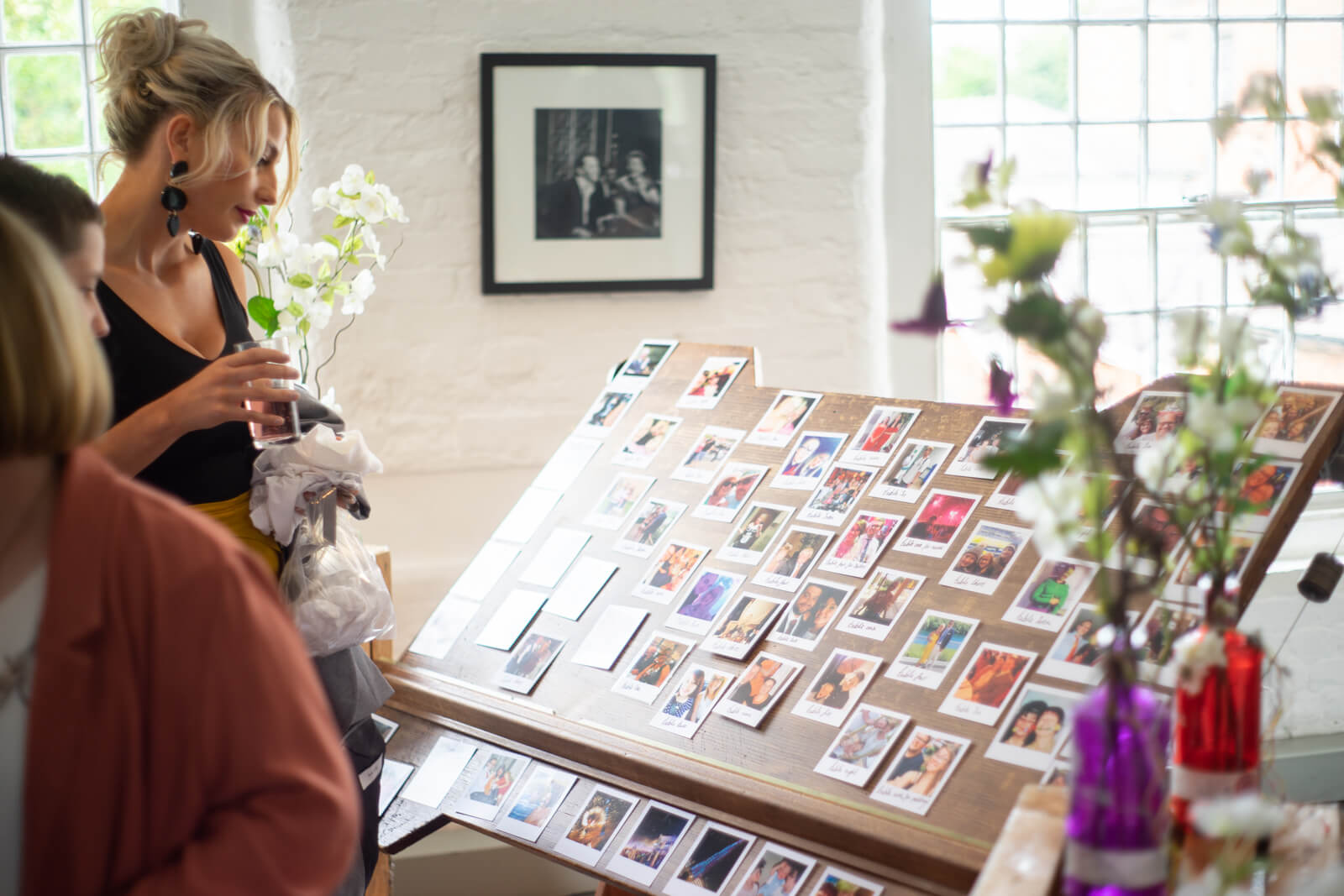Guests look at a seating plan made of polaroid photos on a draftboard