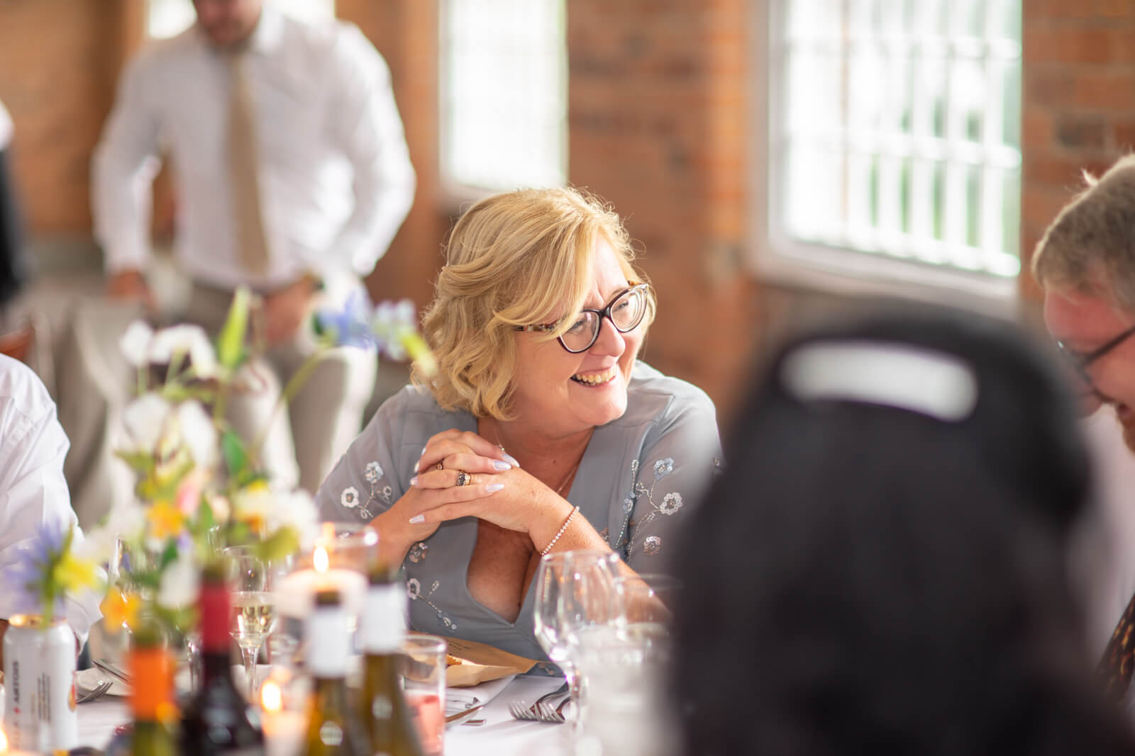 Mother of the bride laughs at a conversation at the dinner table