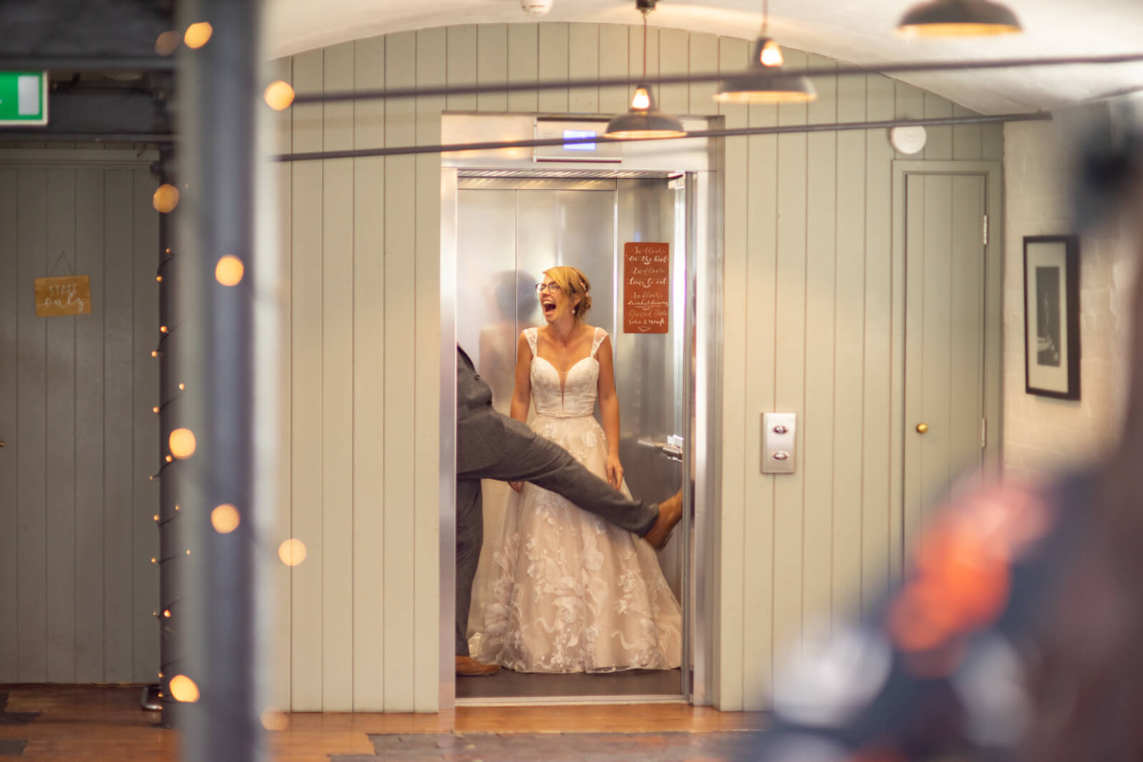Bride laughs as the groom messes about whilst exiting the lift