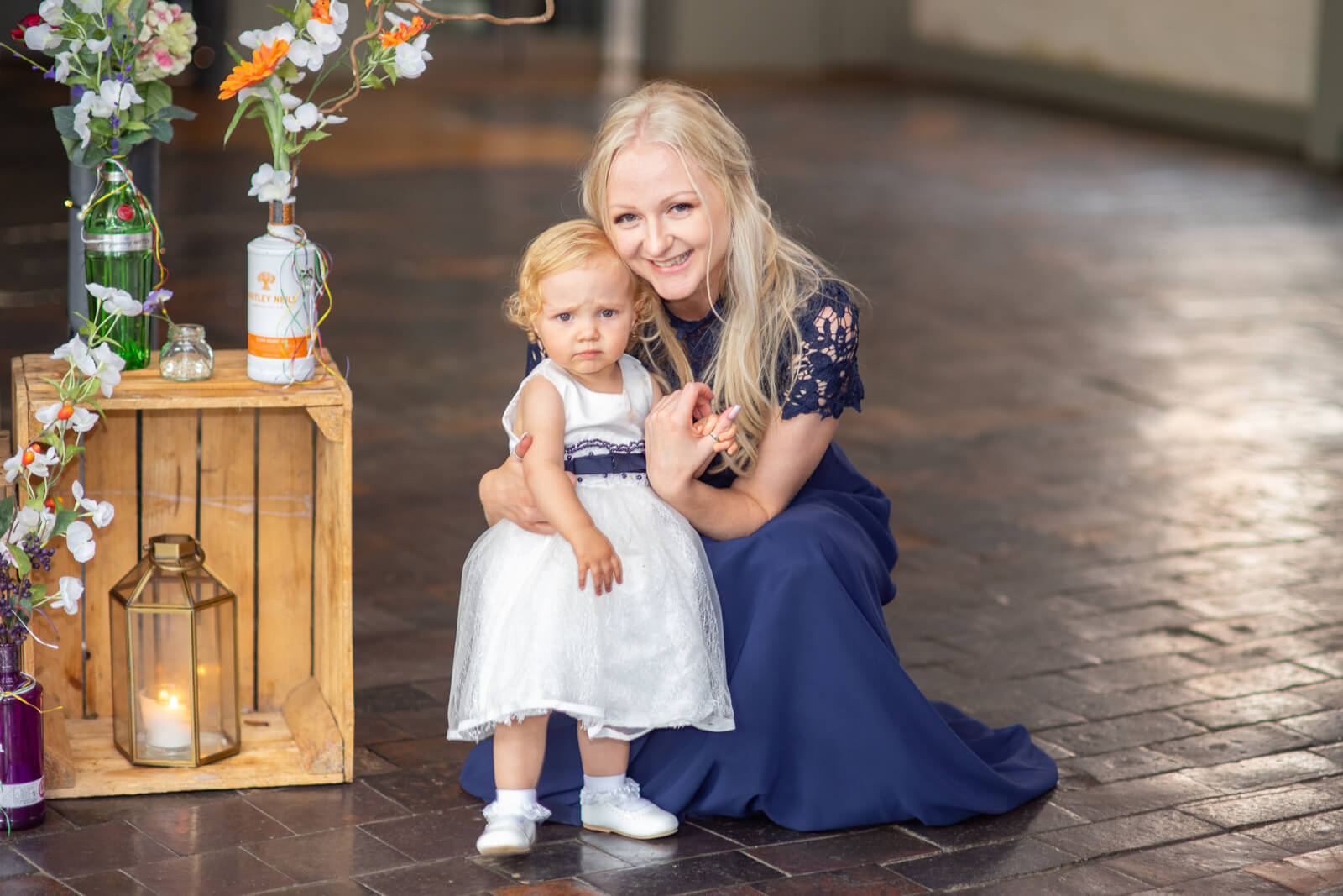Bridesmaid crouches down and poses with her baby daughter in a pretty white dress