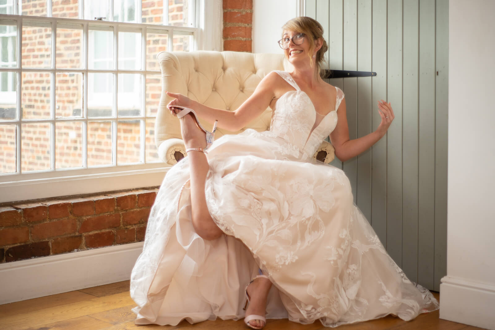 Bride strikes a silly pose after putting her shoes on