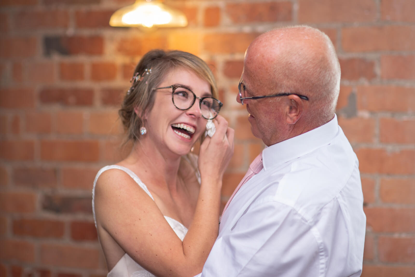 Bride wipes tears away and smiles while she dances with her dad