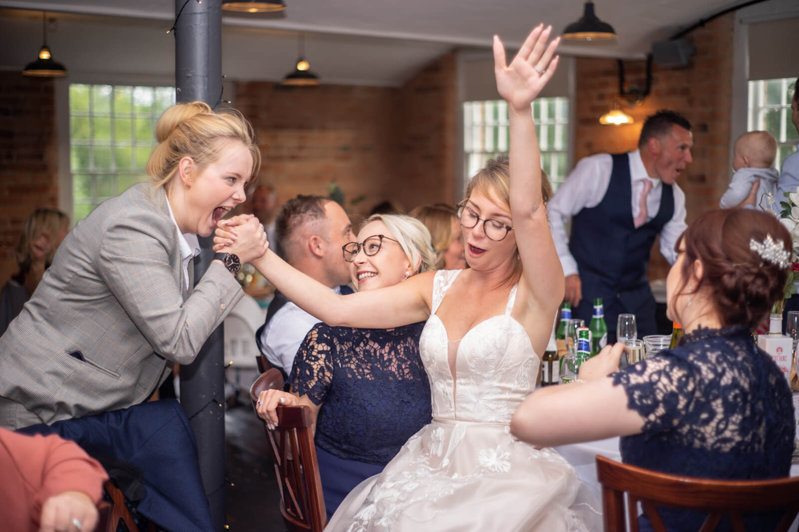 Bride and her friends sing together during the wedding breakfast