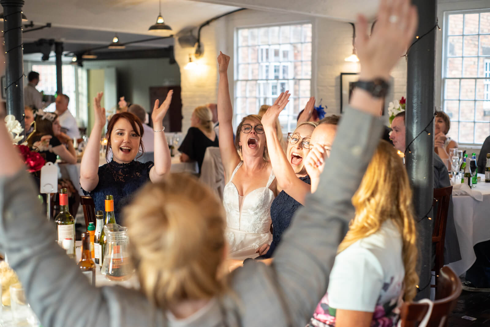 Bride sits around a table with her friends they all throw their arms in the air cheering
