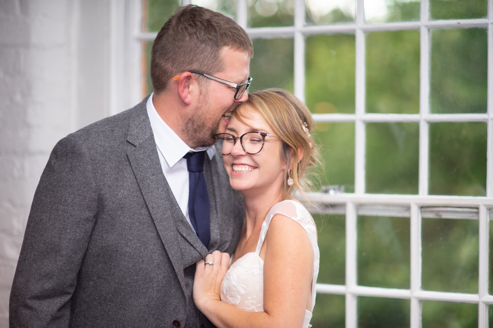 Bride and groom laugh while having their portrait taken against a window