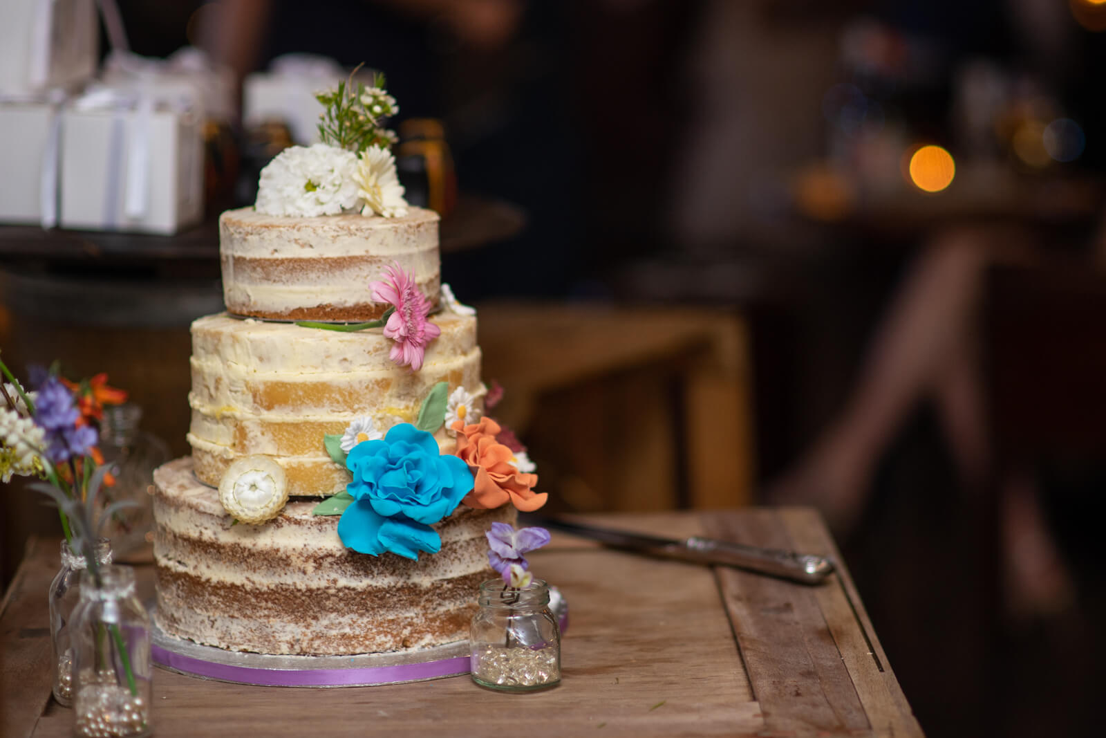 Naked wedding cake with colourful flower decorations