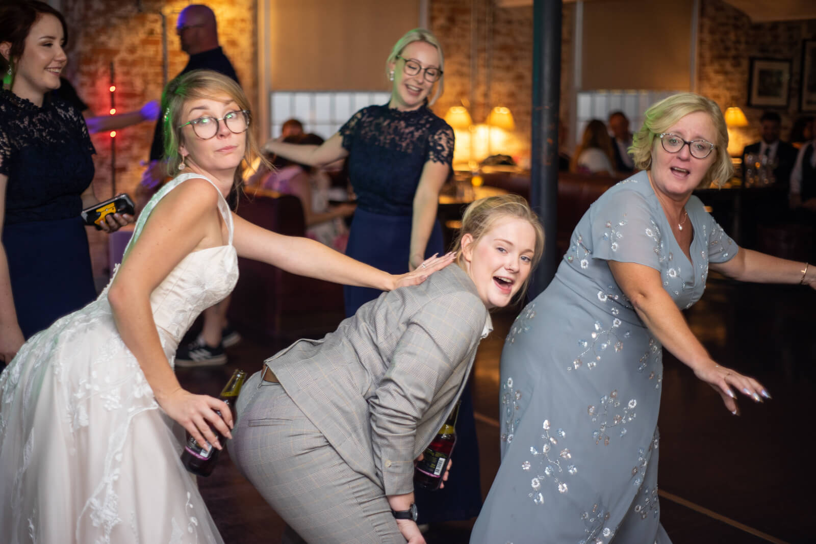 Bride, her mum and friends mess about on the dance floor