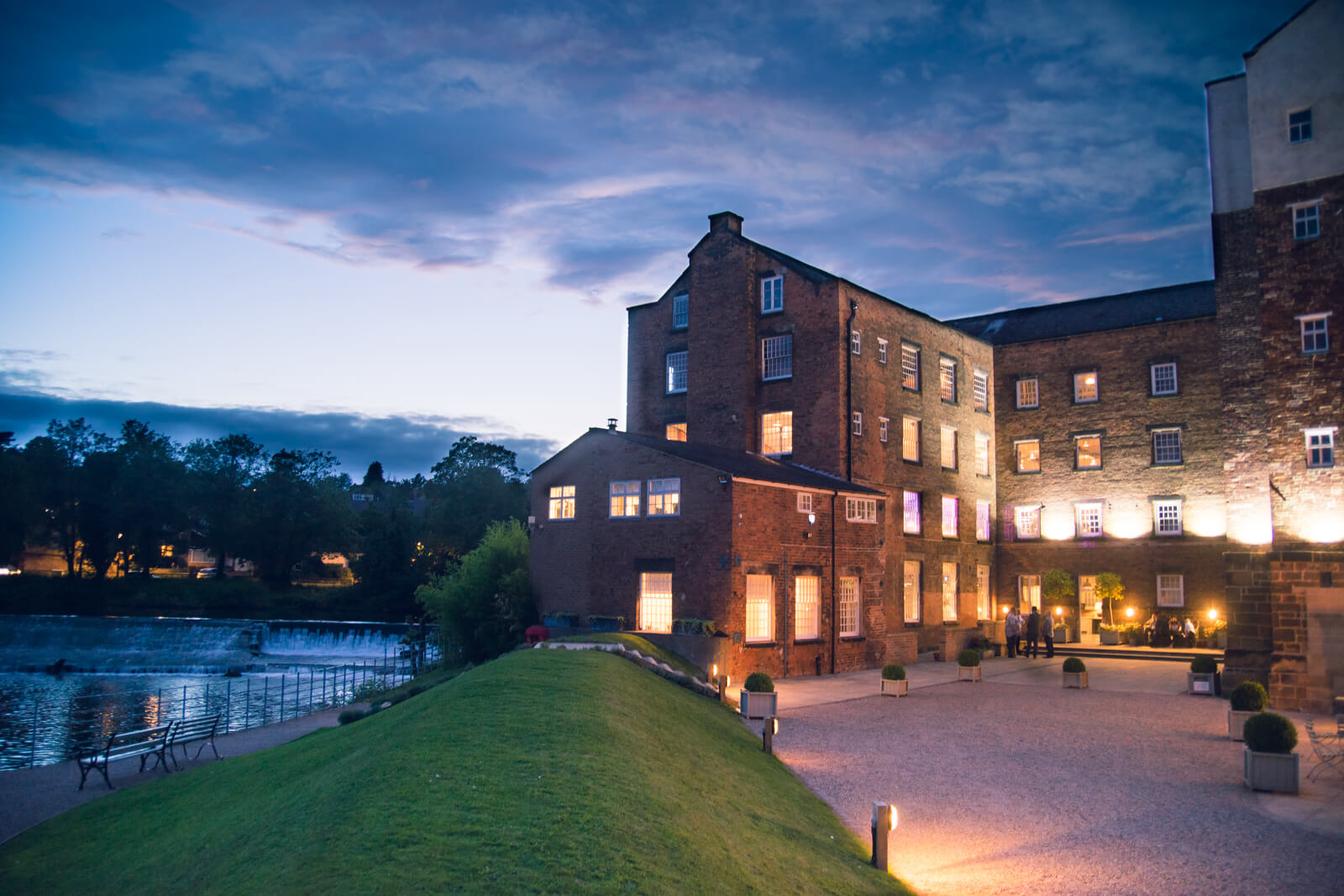 The West Mill Wedding Venue lit up at night by the derwent river