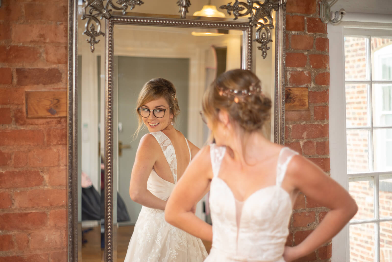 Bride looks at the back of her dress in a mirror
