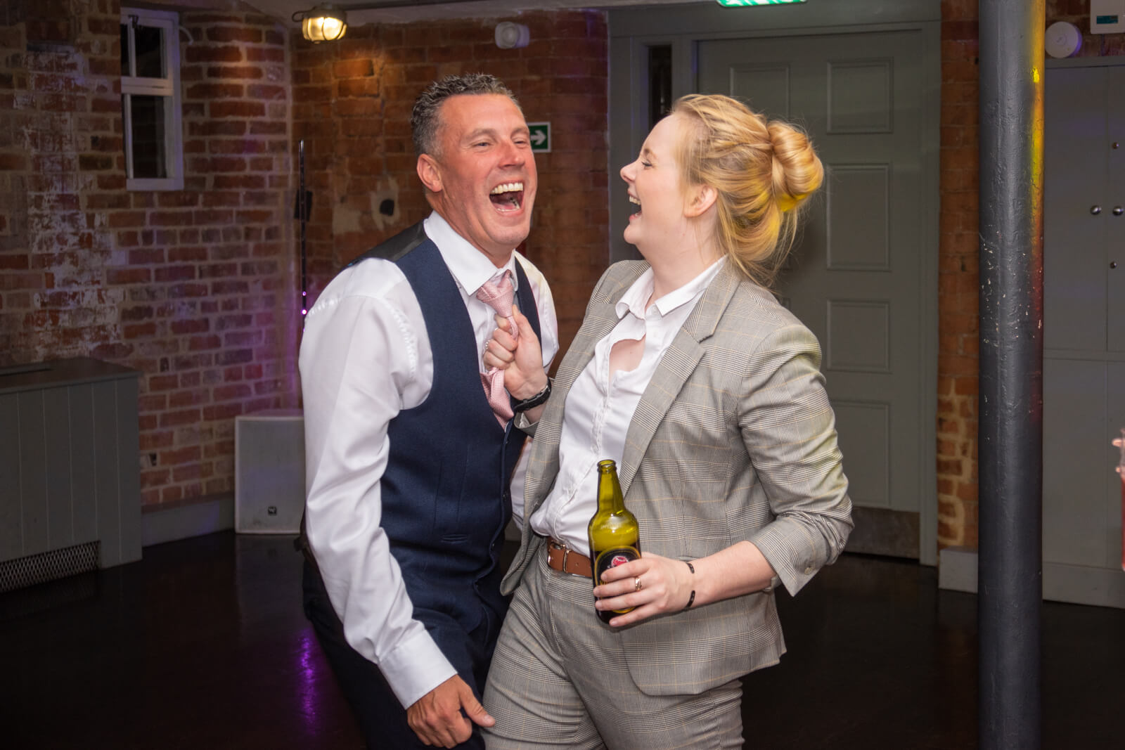 Wedding guests laugh together as one grabs the other by the tie