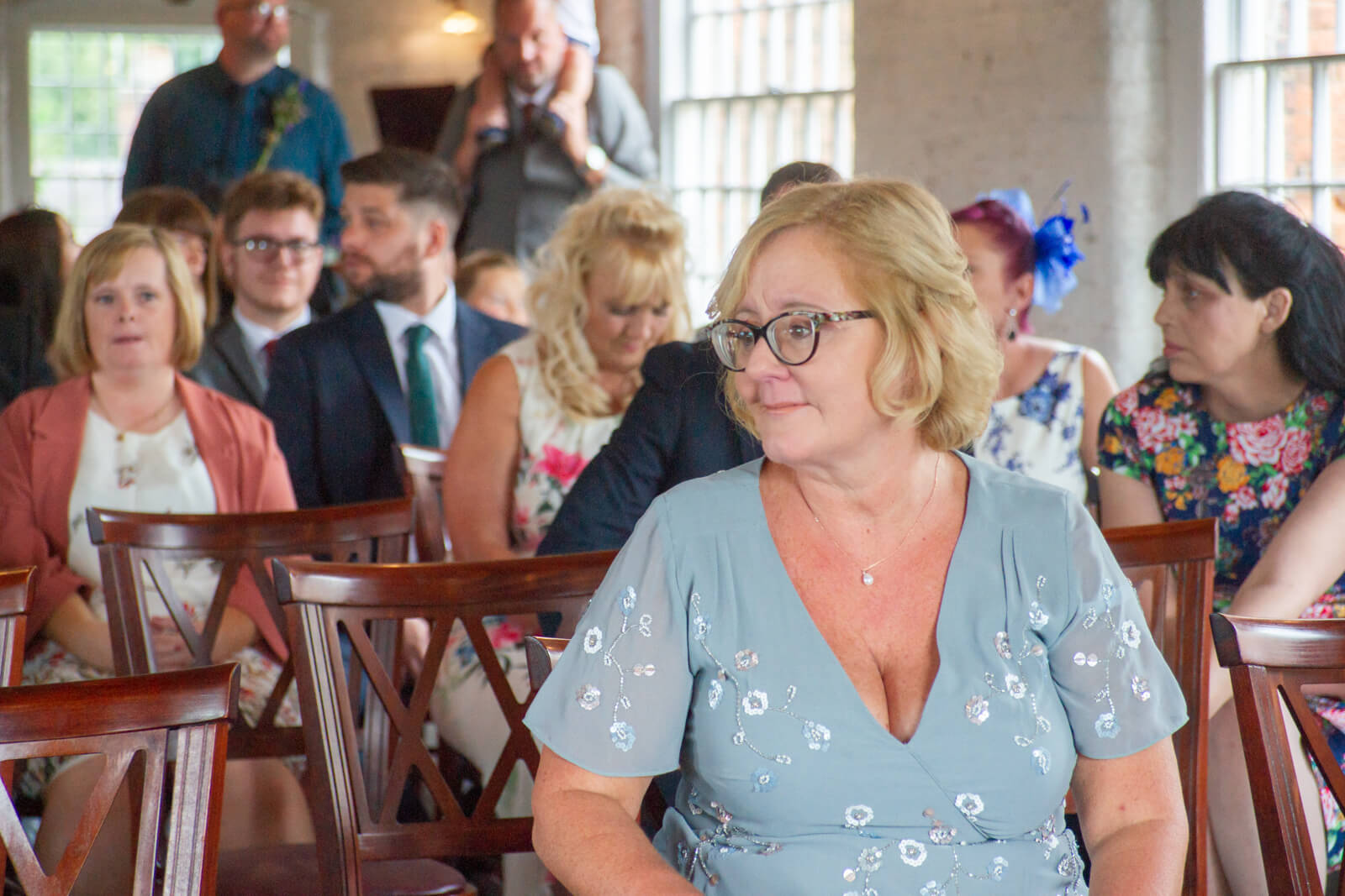 Mother of the bride looks emotional whilst waiting for the ceremony to start
