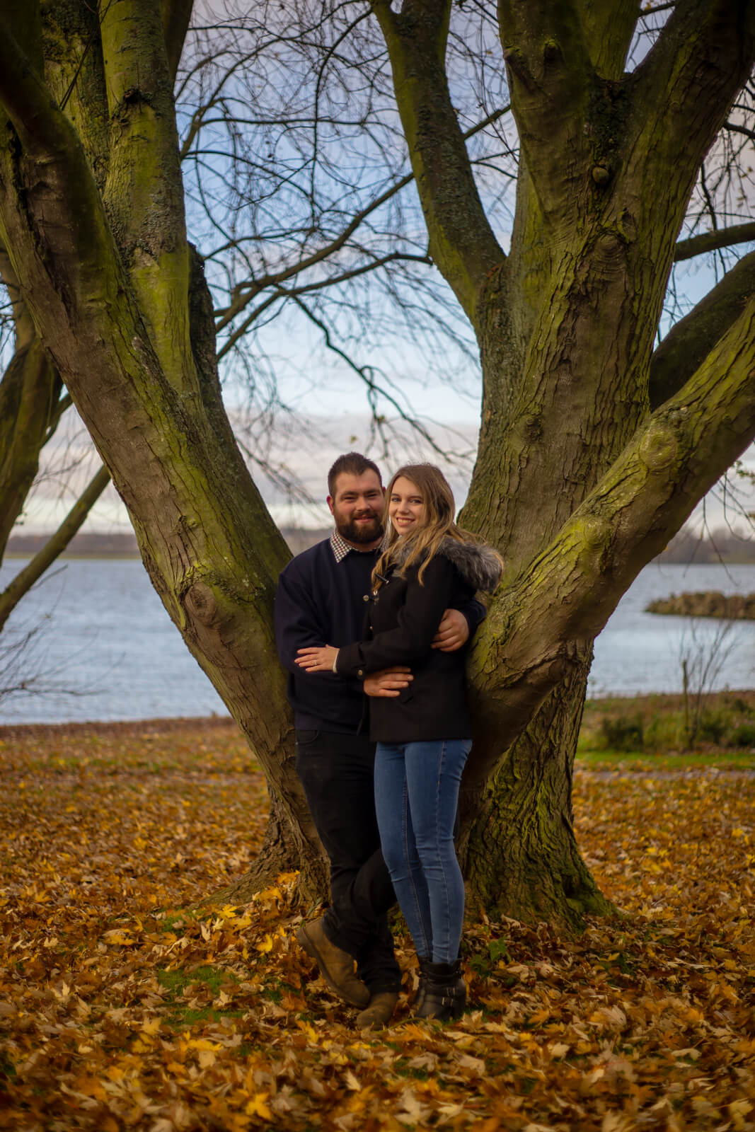 Young couple standing in front of a forked tree by a lake