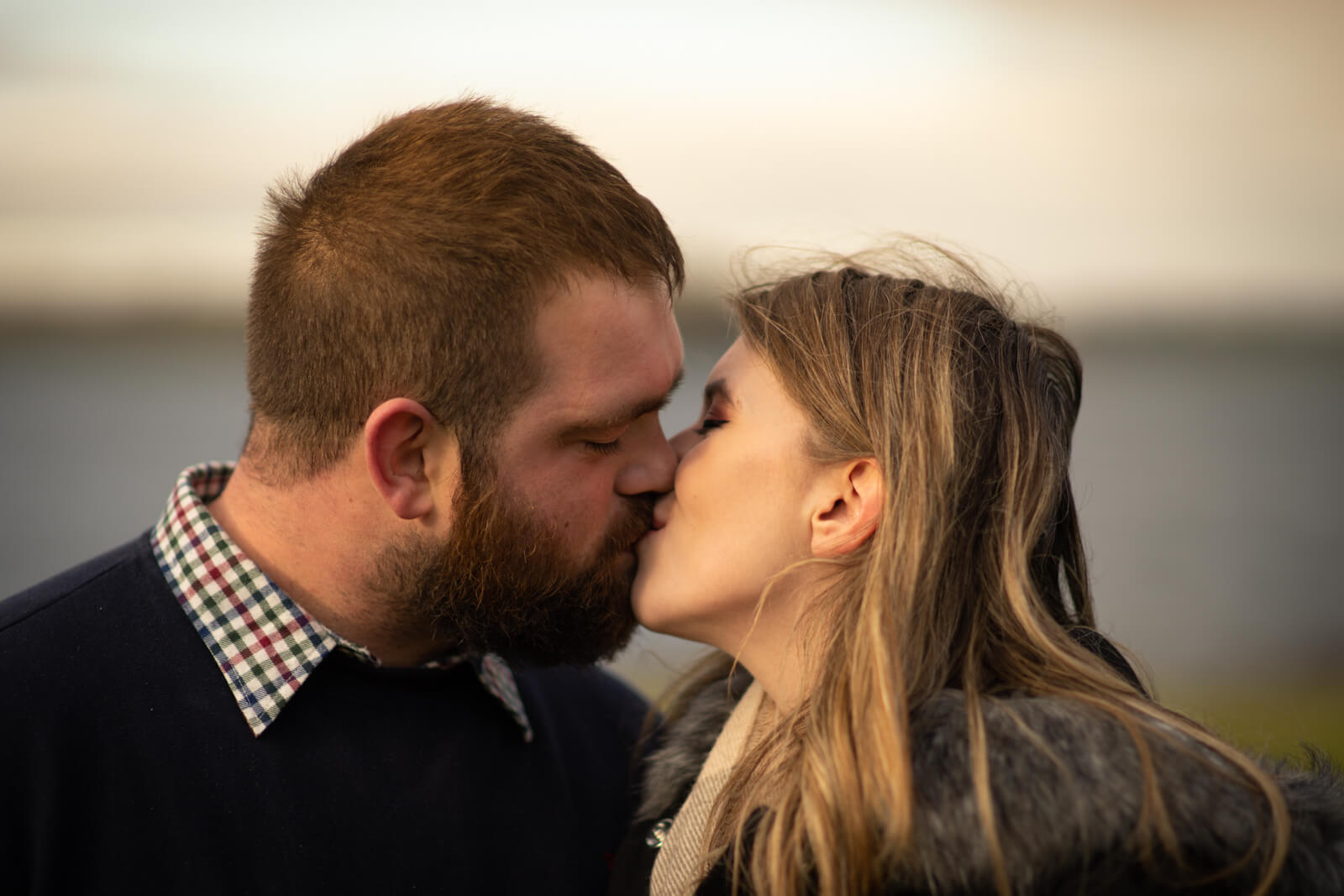 Doodah Photography. Young engaged couple kiss under a winter sky