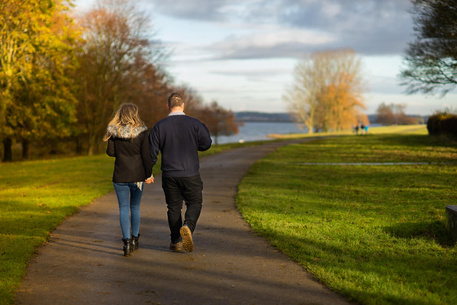 Engagement photo of a couple walking away down a lakeside pathway