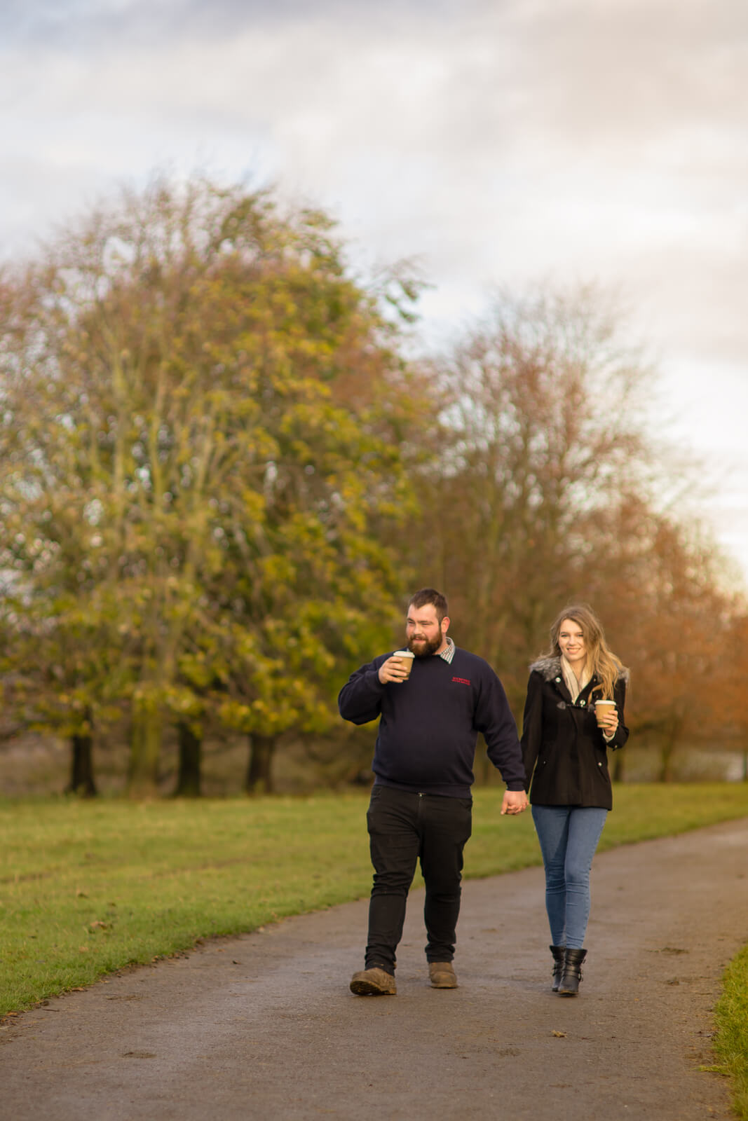 Couple walking down a tree lined path with cups of coffee