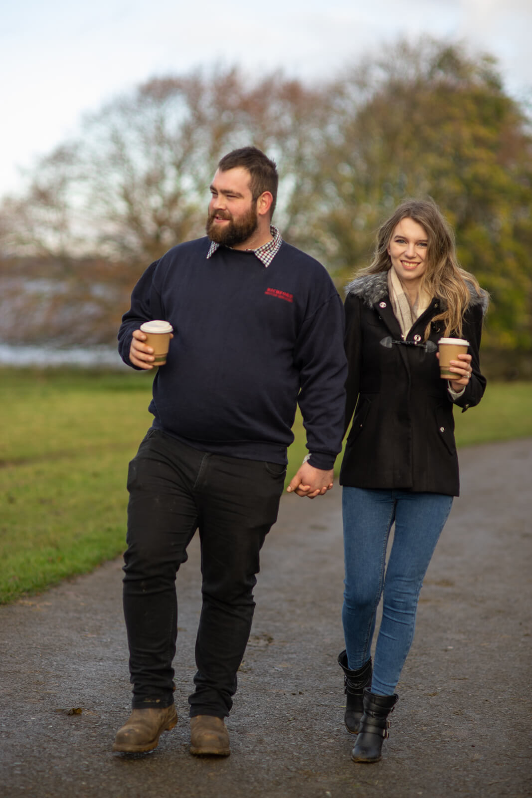 Young couple holding hands and walking with cups of coffee
