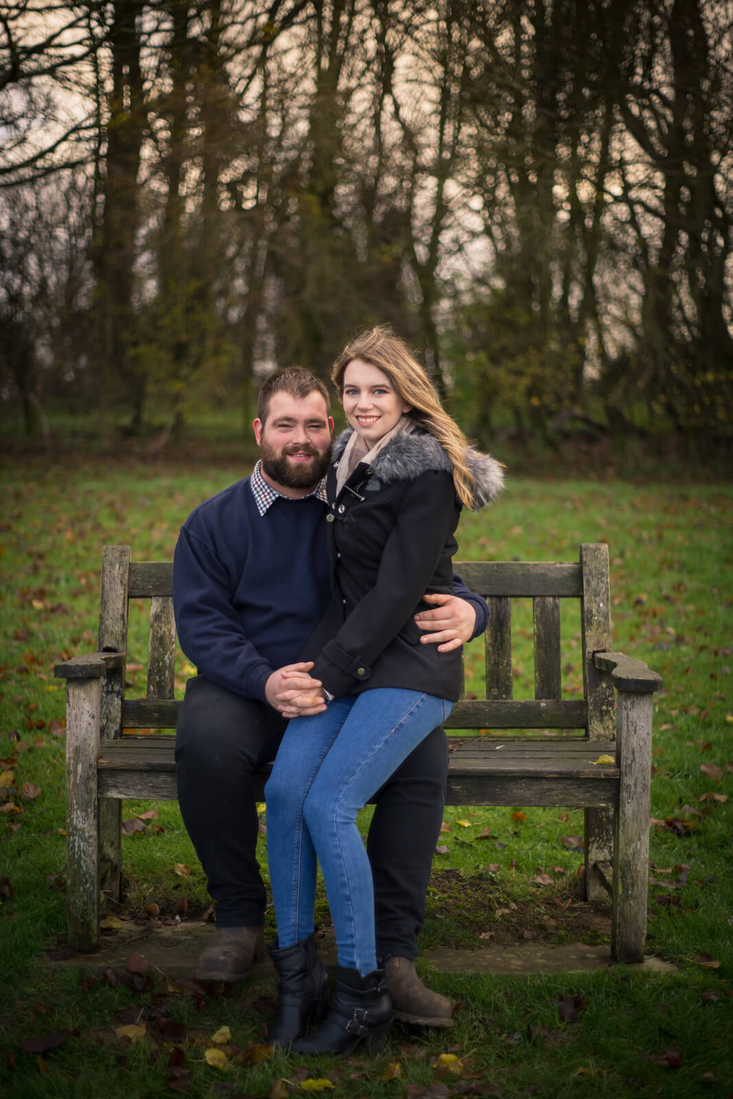 Man sits on a park bench with his fiance on his knee