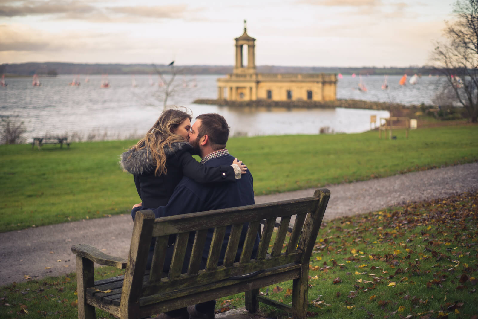 Engaged couple kiss on a bench with Normanton Church in the background