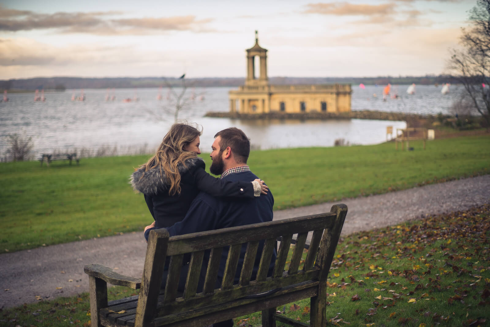 Couple sit on a bench looking at each other with lake and church in the background