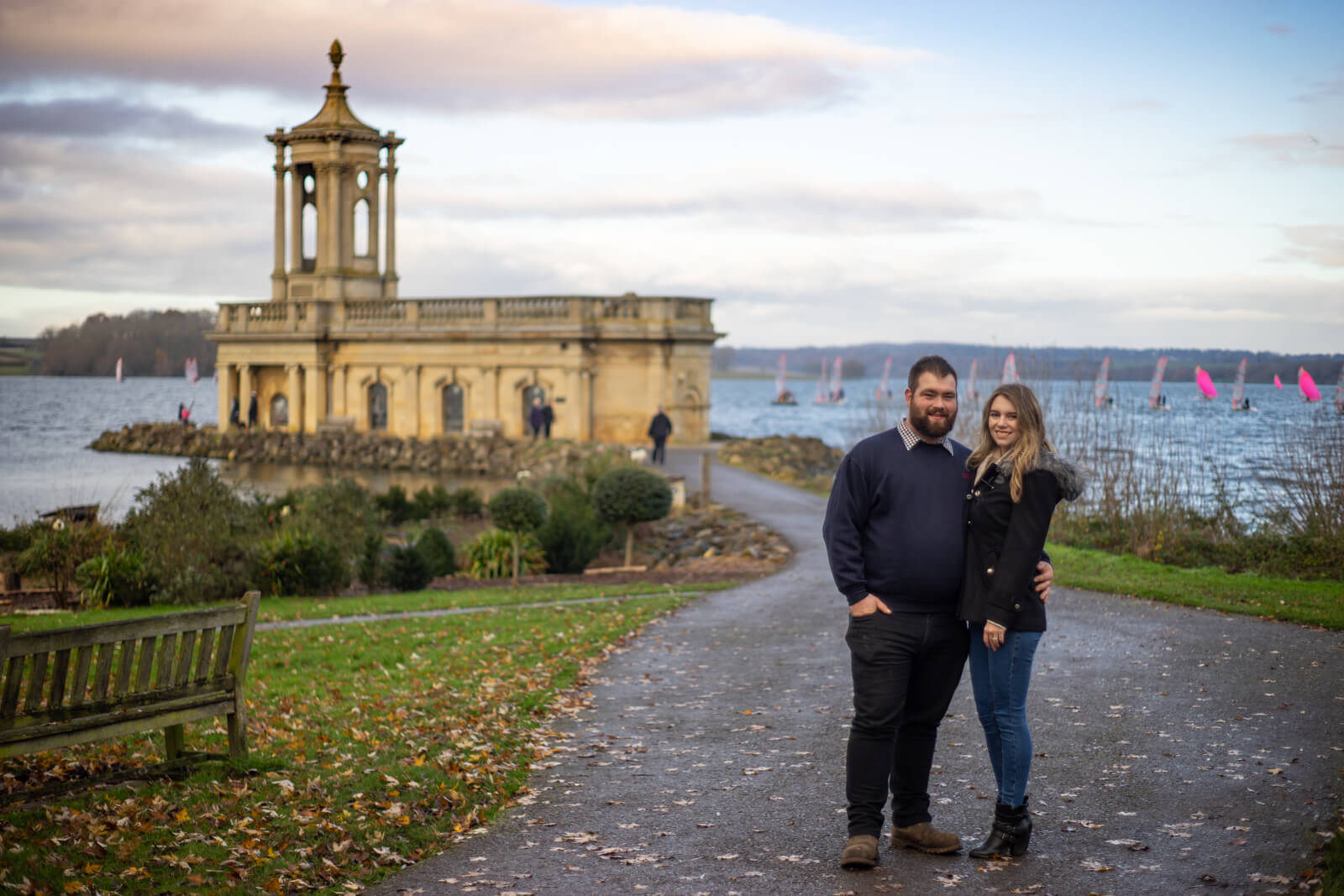 Young couple stand together in front of Normanton Church with windsurfers on the lake