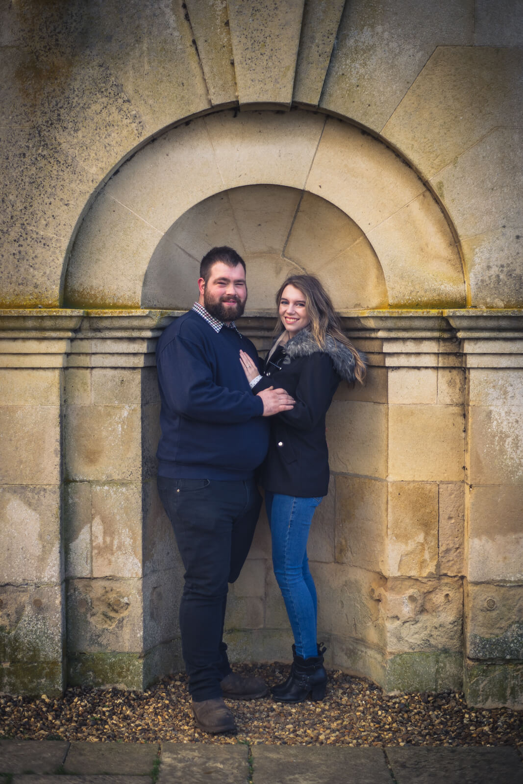 Young couple stand in a stone arch together