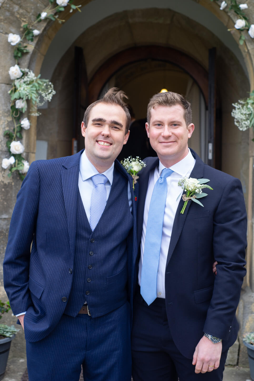 Groom and his best man standing together outside the chapel