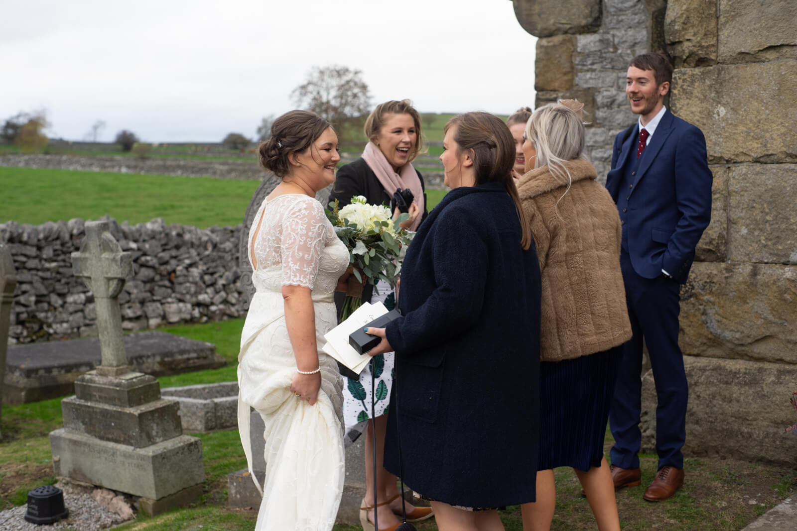 Bride and her friends talking in the churchyard
