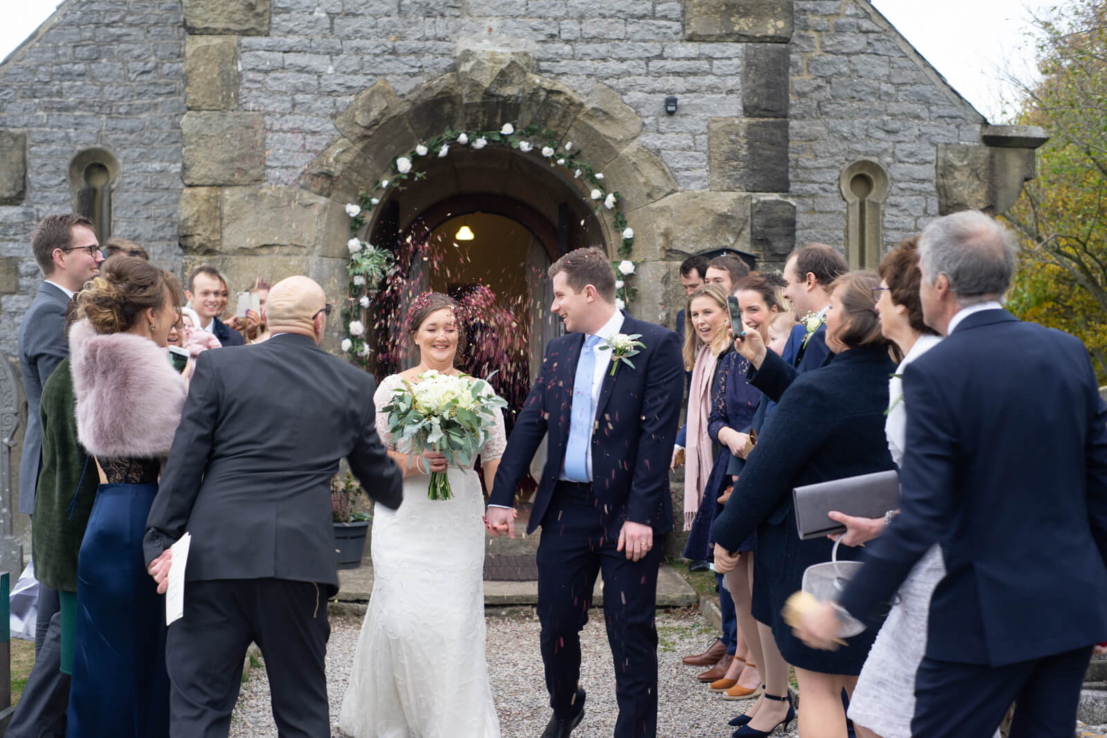 Bride and groom walk through their guests and are showered with confetti outside the chapel