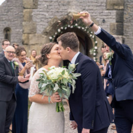 Bride and groom kiss outside thechapel whilst their guests throw confetti