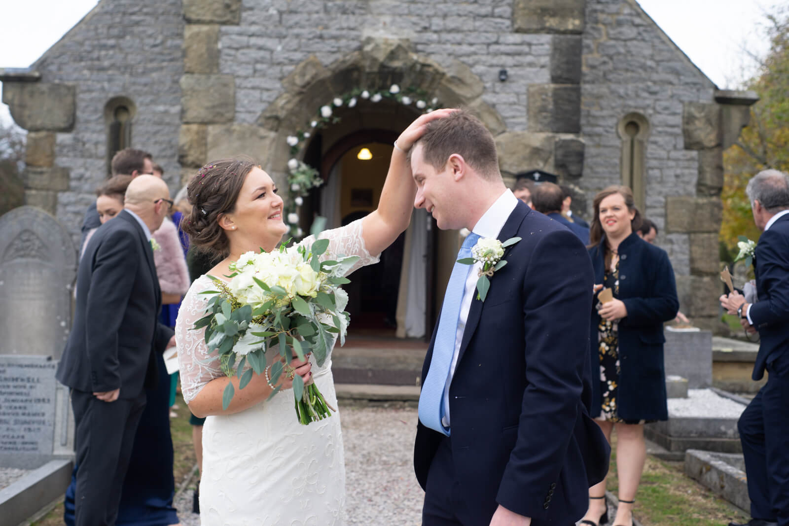 Bride brushes confetti from the grooms hair outside the chapel