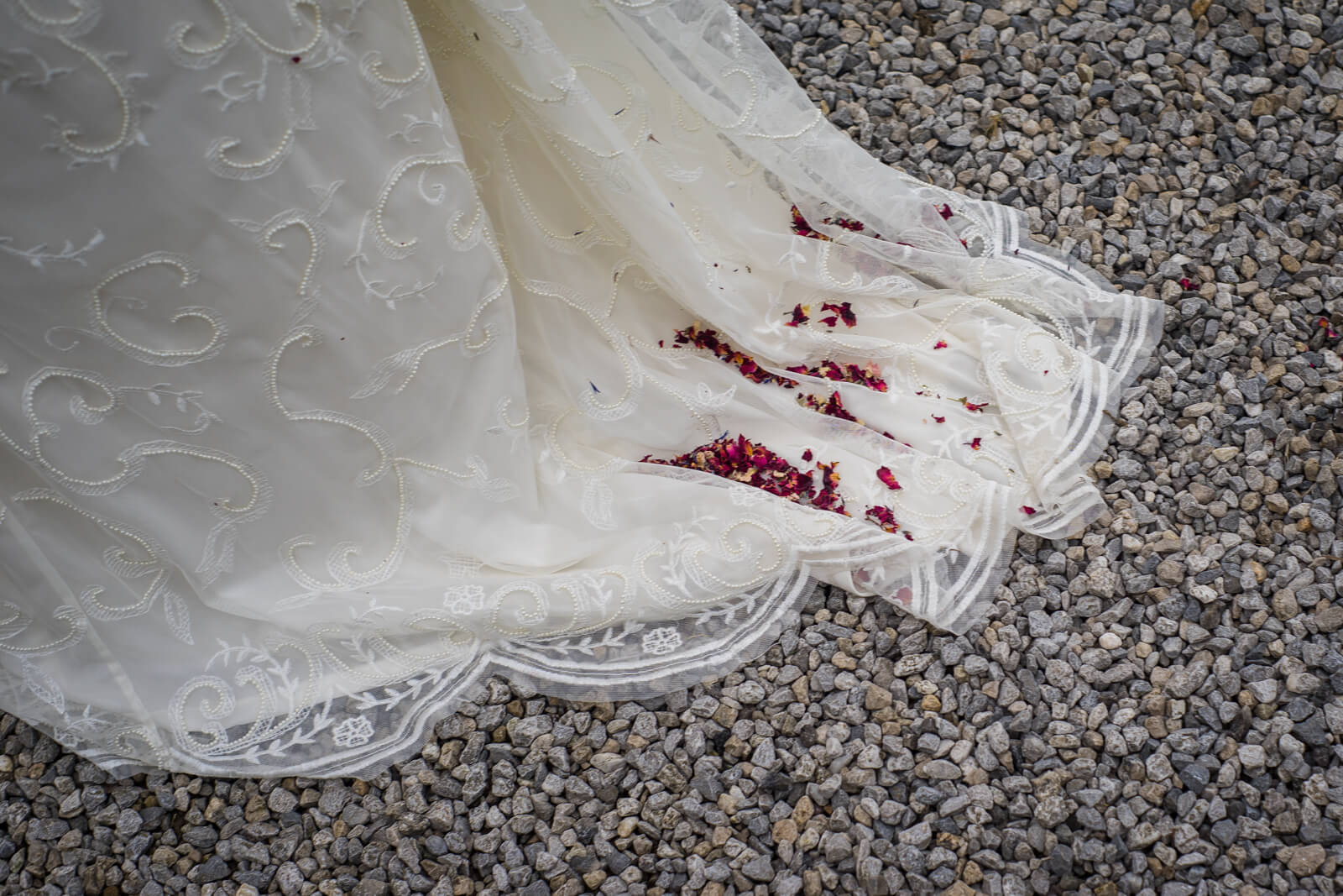 Bride's train against gravel with dried petal confetti on it