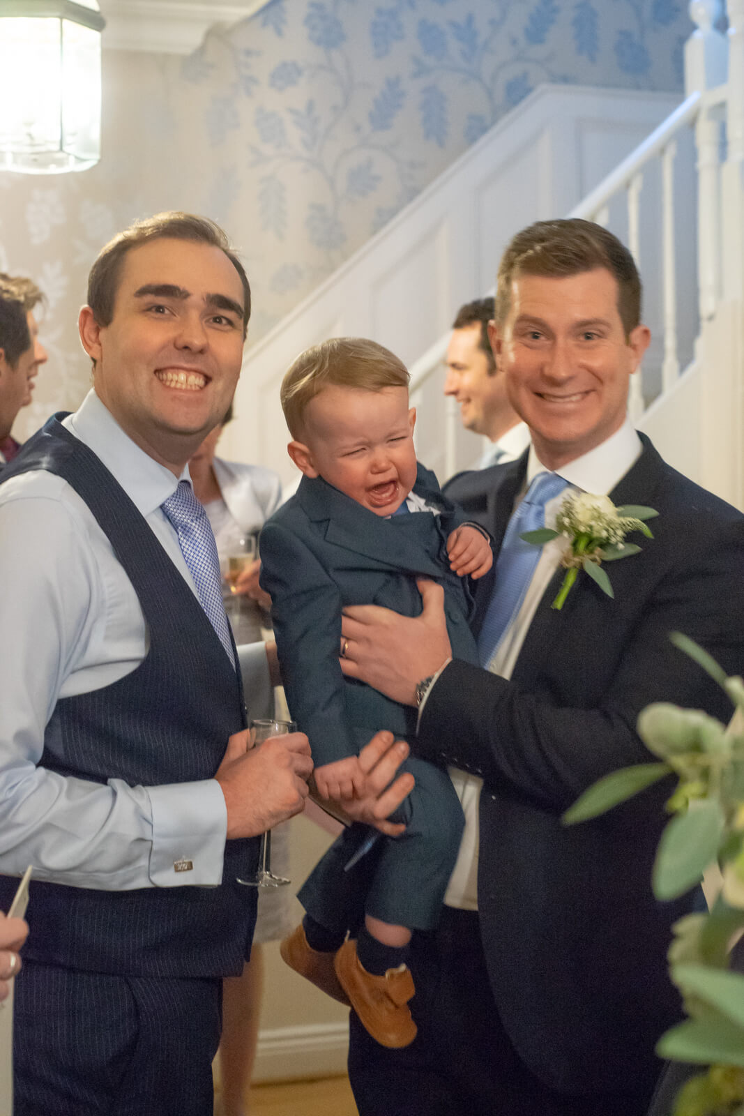 Groom and best man grin at the camera while young toddler between them screams