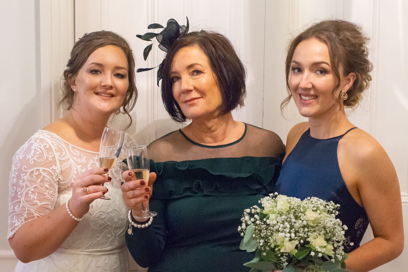 Mother of the bride and her daughters pose with champagne