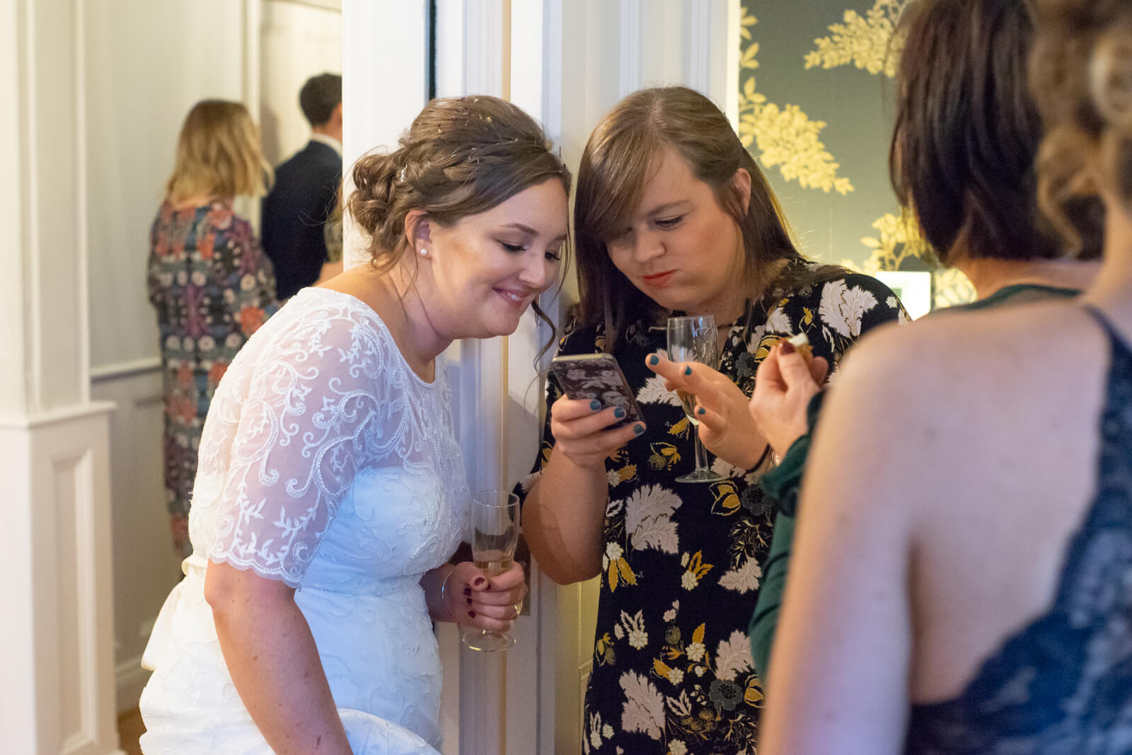 Bride and her friend laugh while looking at a mobile phone