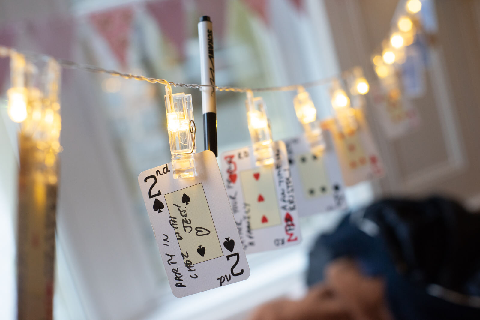 Wedding decorations of playing cards with guests' messages hang from a string of fairy lights