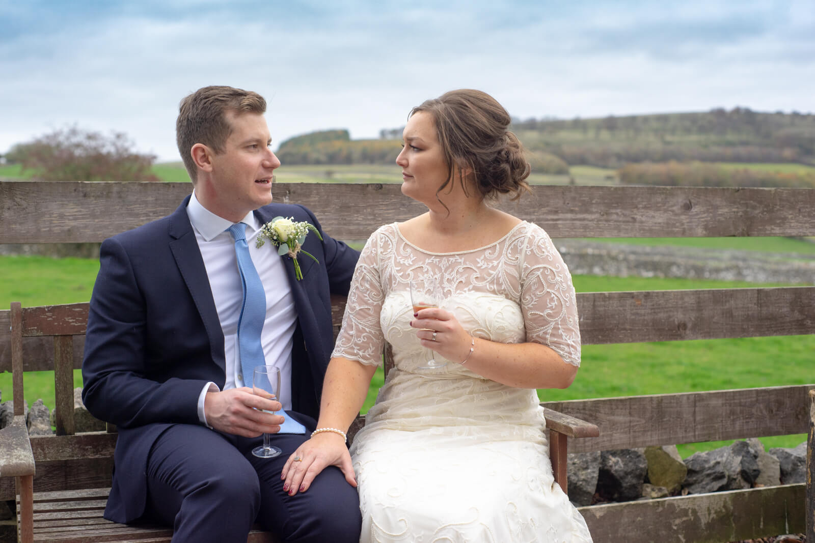 Bride and groom sit talking on a bench in front of the derbyshire countryside