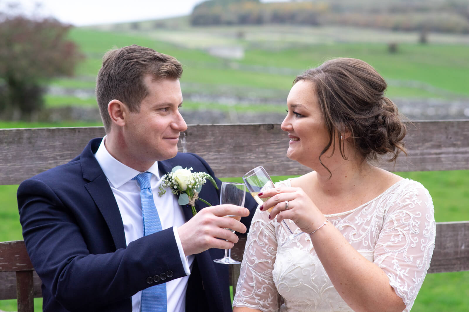 Bride and groom clink glasses and smile at each other while sitting outside
