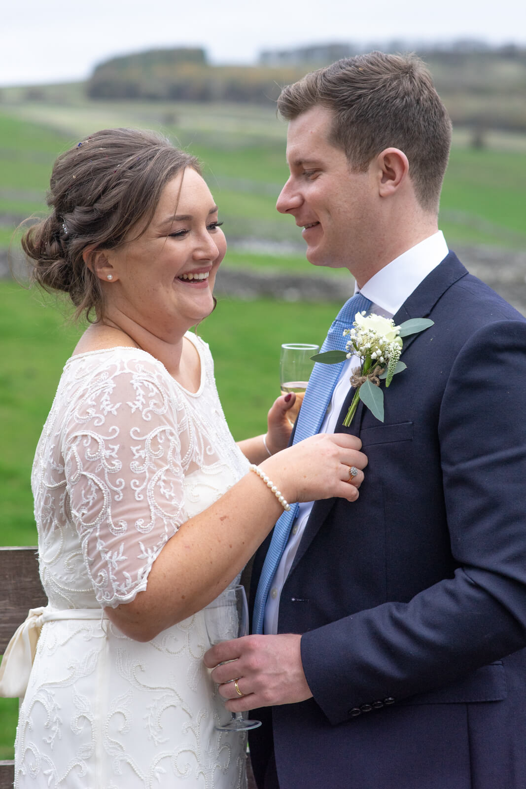 Bride and groom laugh together in the derbyshire countryside
