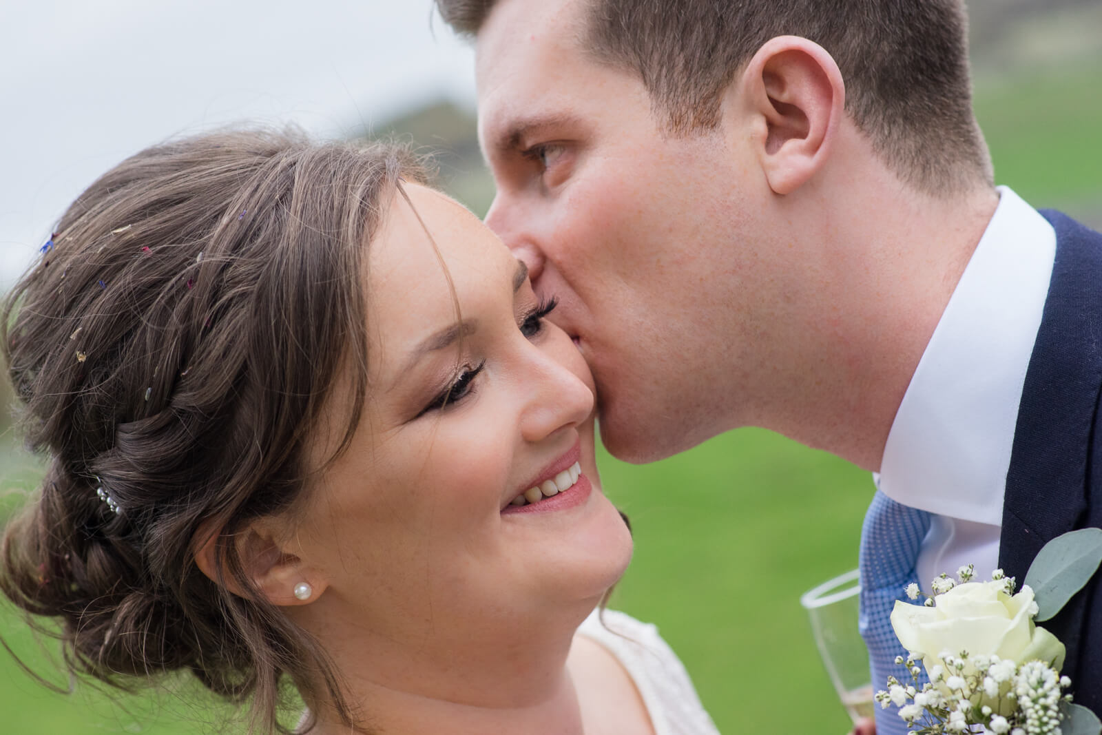 Close up portrait of the bride and groom taken as he kisses her on the cheek