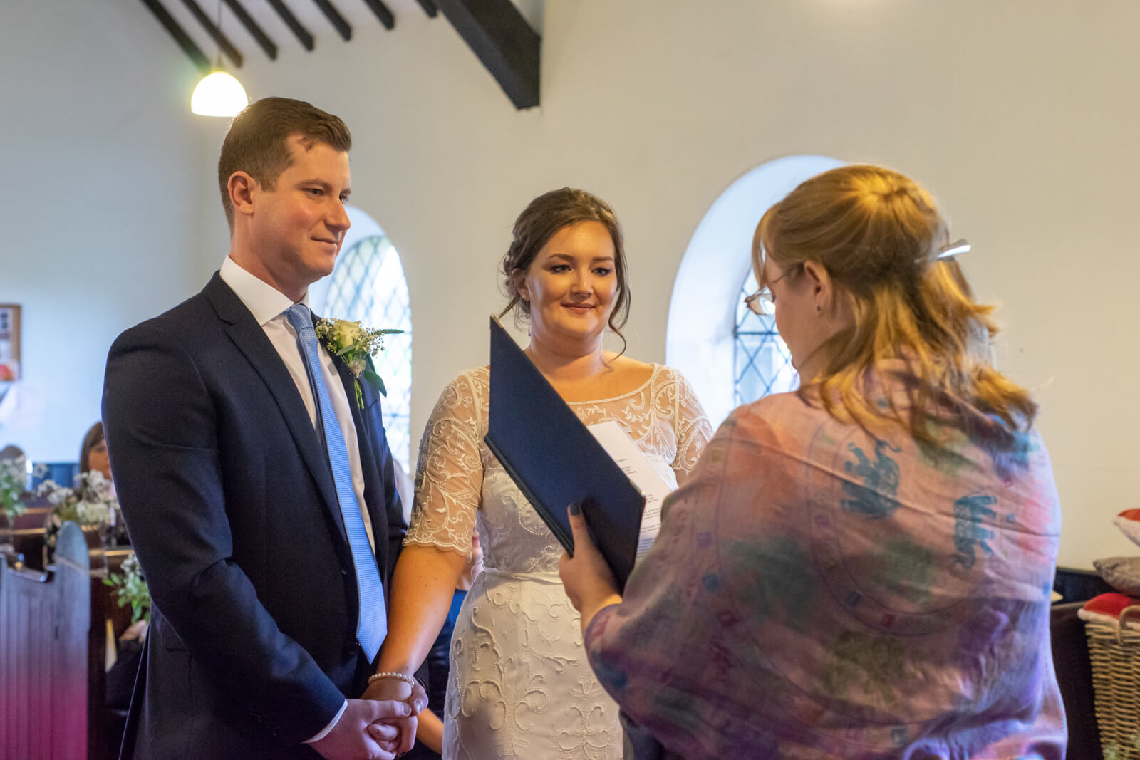 Bride and groom hold hands at the alter while celebrant conducts the service