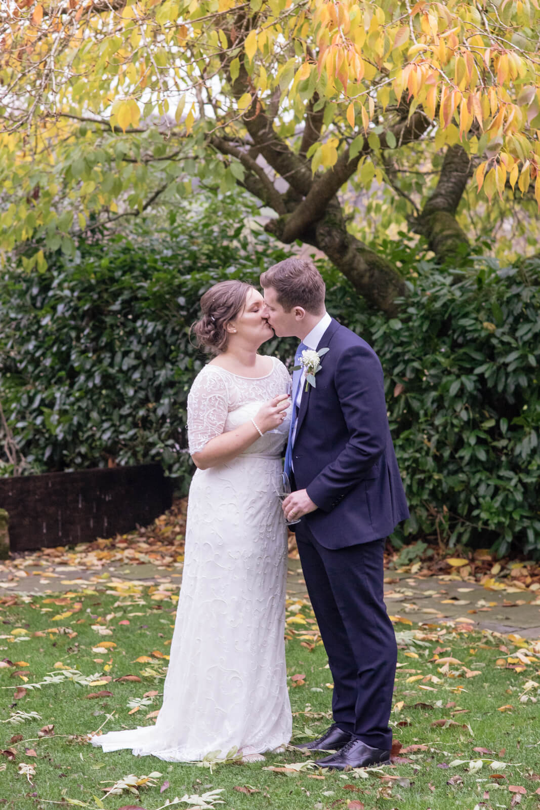 Bride and groom stand kissing under a tree with yellow leaves