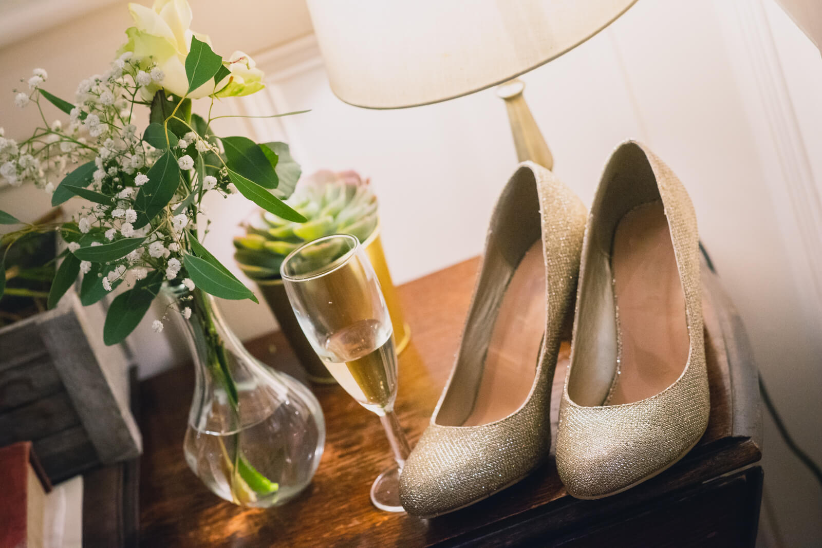 Bride's shoes, flowers and a champagne glass lit by a table lamp on a side table