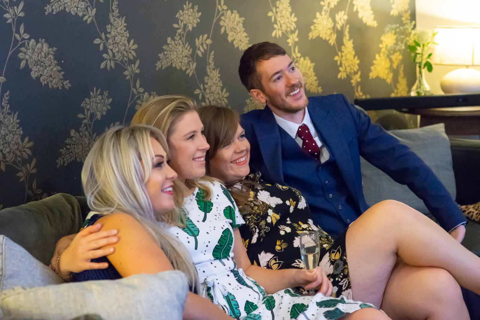 Group of four friends huddle together on a sofa for a photo