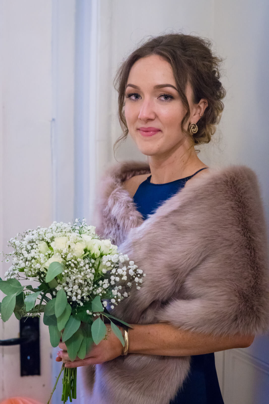 Bride's sister poses for a portrait with bouquet and fur wrap
