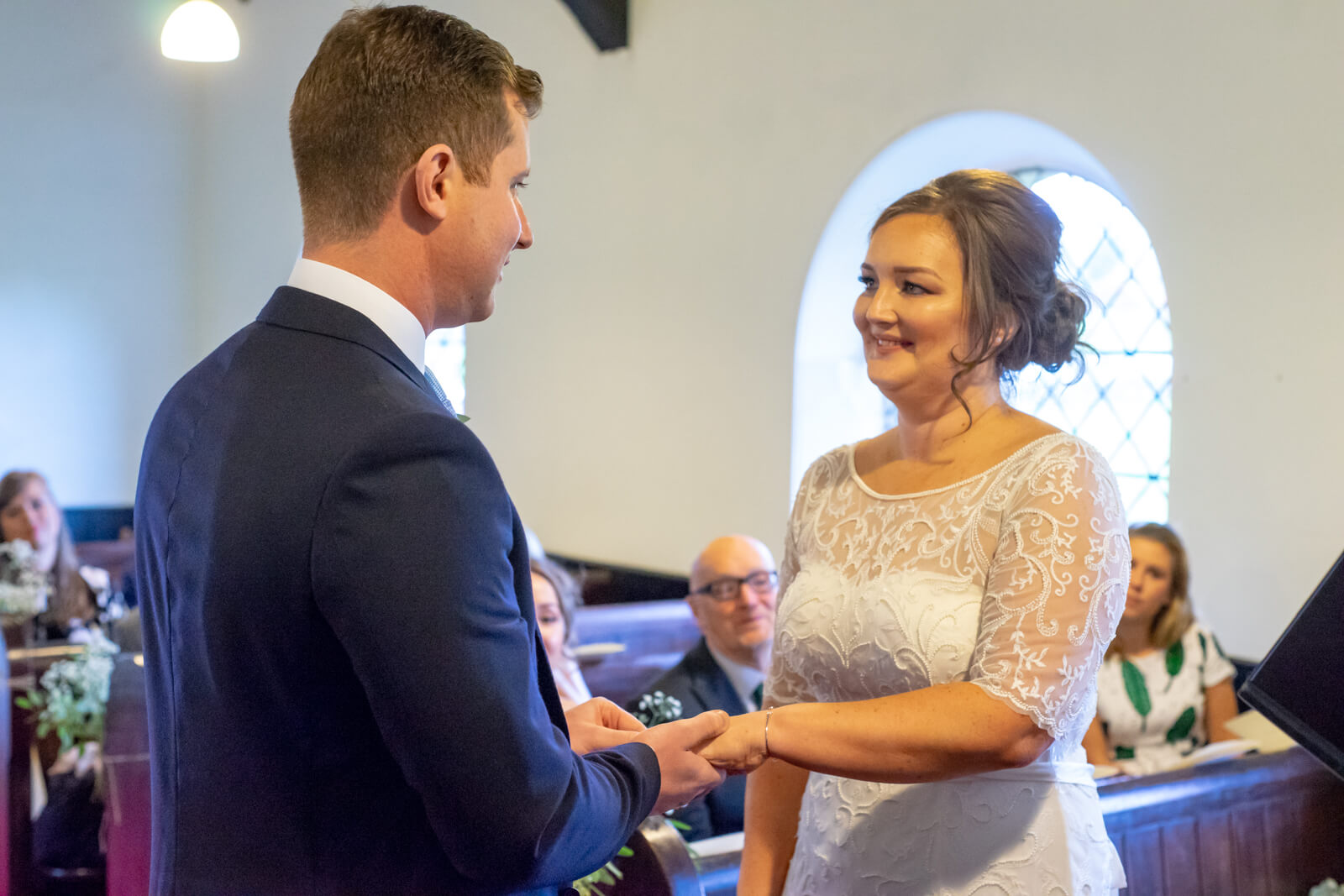 Bride and groom hold hands while they say their vows